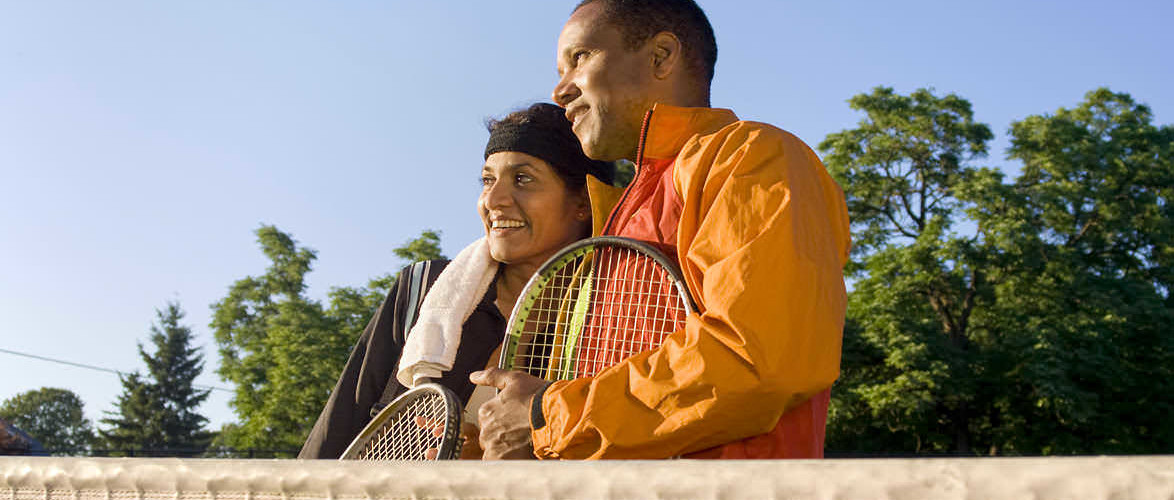 Tennis couple standing at the net. Horizontal